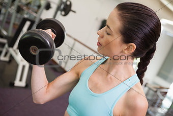 Fit brunette lifting heavy dumbbell