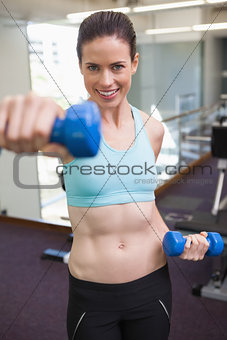 Fit brunette lifting blue dumbbell