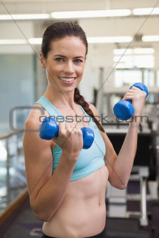 Fit smiling brunette lifting blue dumbbells