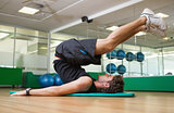 Fit man doing pilates in fitness studio
