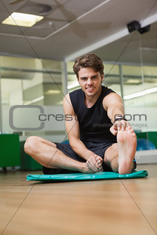 Fit man warming up in fitness studio