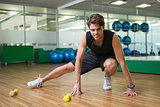 Fit smiling man warming up in fitness studio