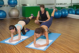 Fit women in pilates position with trainer watching