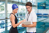 Swimmer discussing times with her coach by the pool