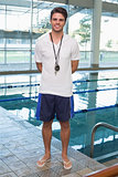 Swimming coach standing by the pool smiling at camera