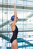 Pretty swimmer stretching arms by the pool