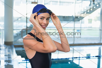 Pretty swimmer smiling at camera by the pool
