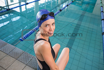 Fit swimmer sitting by the pool smiling at camera
