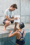 Swimmer talking to her coach poolside
