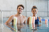 Man and woman standing with foam rollers in the pool