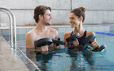 Man and woman standing with foam dumbbells in the pool