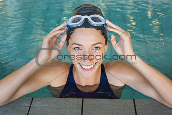 Fit swimmer smiling up at camera in the swimming pool