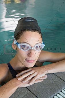 Fit swimmer looking at camera in the swimming pool