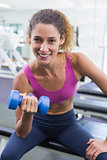 Pretty fit woman lifting blue dumbbell smiling at camera