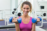 Pretty fit woman lifting blue dumbbells smiling at camera