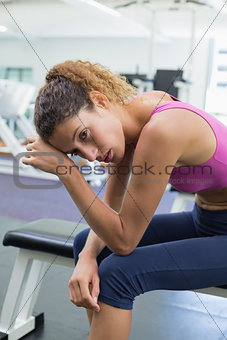 Tired fit woman taking a break on the bench