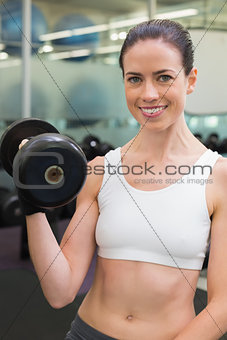 Fit smiling brunette lifting heavy black dumbbell