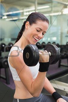 Fit smiling brunette lifting heavy black dumbbell