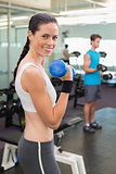Fit brunette lifting blue dumbbell smiling at camera