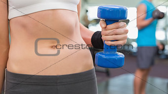 Fit woman holding blue dumbbell mid section