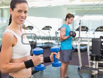 Fit brunette exercising with blue dumbbells