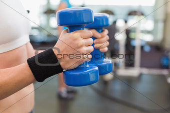 Fit woman exercising with blue dumbbells