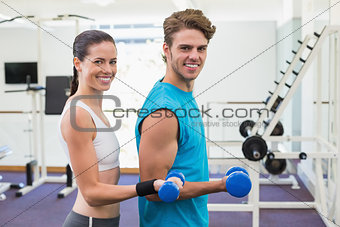Fit couple exercising with blue dumbbells smiling at camera