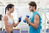 Fit smiling couple exercising with blue dumbbells