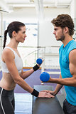 Fit focused couple exercising with blue dumbbells