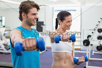 Fit couple exercising with blue dumbbells and smiling