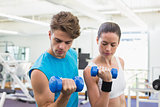 Fit couple exercising together with blue dumbbells