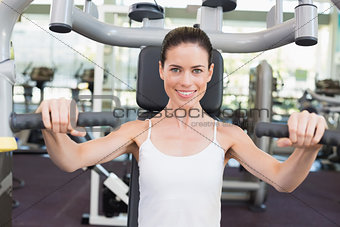 Fit brunette smiling at camera using weights machine for arms