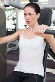 Fit brunette using weights machine for arms