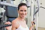 Fit brunette using weights machine for arms smiling at camera