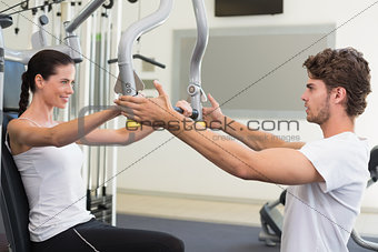 Fit brunette using weights machine for arms with trainer helping