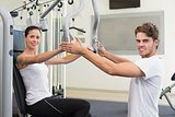 Fit brunette using weights machine for arms with trainer helping smiling at camera