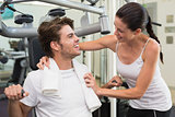 Fit man using weights machine with trainer encouraging him