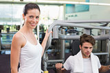 Fit man using weights machine with trainer smiling at camera