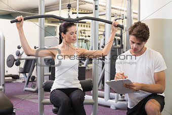 Fit brunette using weights machine for arms with trainer taking notes