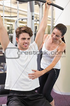 Fit man using weights machine for arms with his trainer