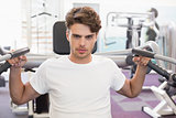 Fit man using weights machine for arms looking at camera