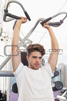 Fit focused man using weights machine for arms