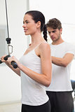 Fit smiling woman using weights machine for arms with her trainer