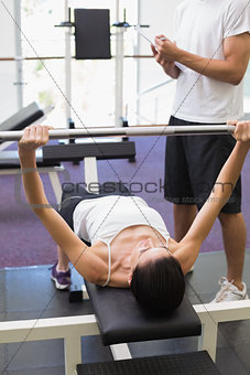 Fit woman lifting barbell with her trainer taking notes