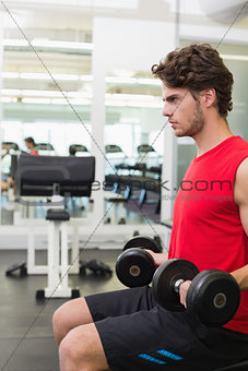 Fit man holding heavy black dumbbells