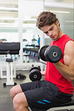 Fit man lifting heavy black dumbbells