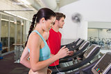 Fit couple running together on treadmills