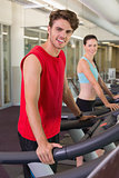 Smilng man and woman on the treadmills