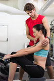 Trainer helping his pretty client on the rowing machine