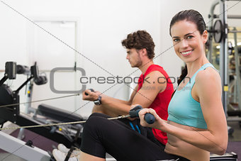 Smiling brunette working out on the rowing machine